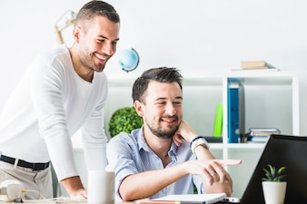 Two smiling young businessmen looking at laptop screen