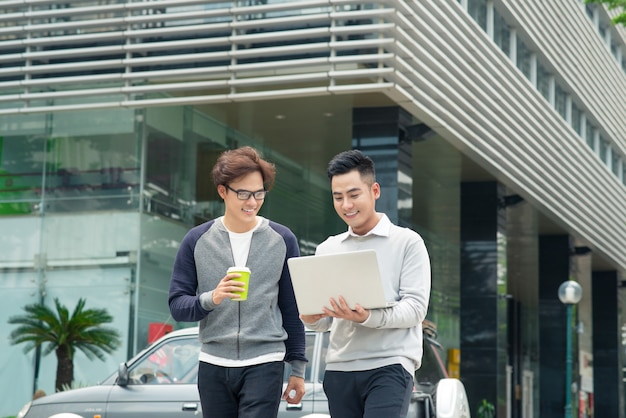 街を歩いて話している 2 人の笑顔の若いビジネスマン
