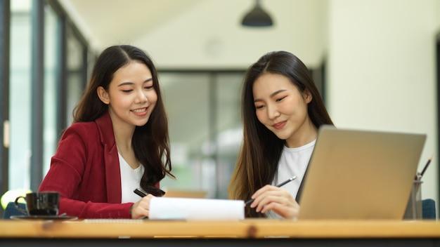 두 명의 웃고 있는 젊은 여성 사업가들이 사무실의 보고서 용지에서 함께 비즈니스 사회적 영향 성과를 분석하고 분석합니다.