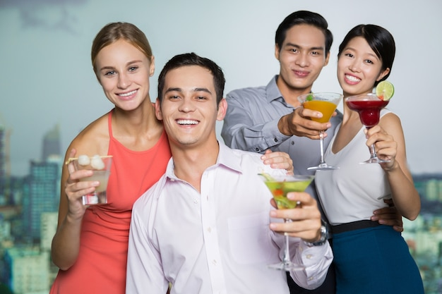 Two smiling young couples with cocktails embracing