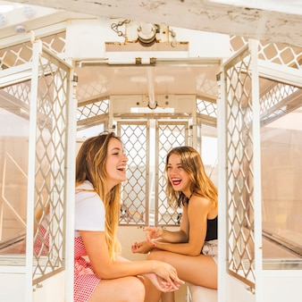 Two smiling young female friend sitting in the ferris wheel cabin