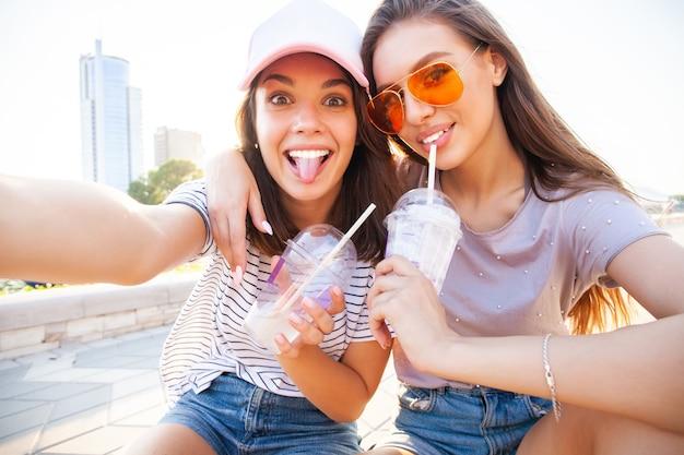 Две улыбающиеся молодые девушки веселятся, сидя на скейтборде и делая селфи в парке