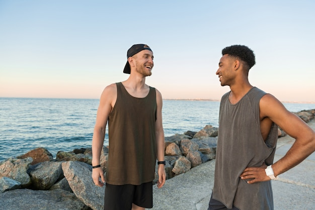 Two smiling young guys in sportswear talking while standing