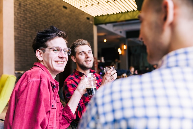 Two smiling young men holding beer glasses looking at their friend