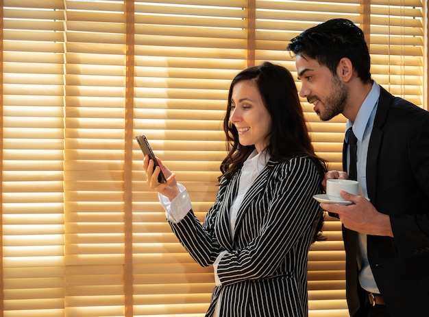 Two smiling young office colleagues wearing suits standing near window and  looking at mobile phone. businesswoman holding smartphone while businessman holding cup of coffee in office.