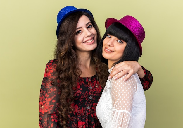 パーティーハットを身に着けている2人の笑顔の若いパーティーの女性は、オリーブグリーンの壁に隔離された正面を見て両方の肩でもう1つを保持しています