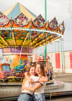 Two smiling young woman embracing in front of illuminated colorful carousel
