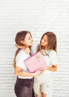 Two smiling young women holding birthday gift in front of wall