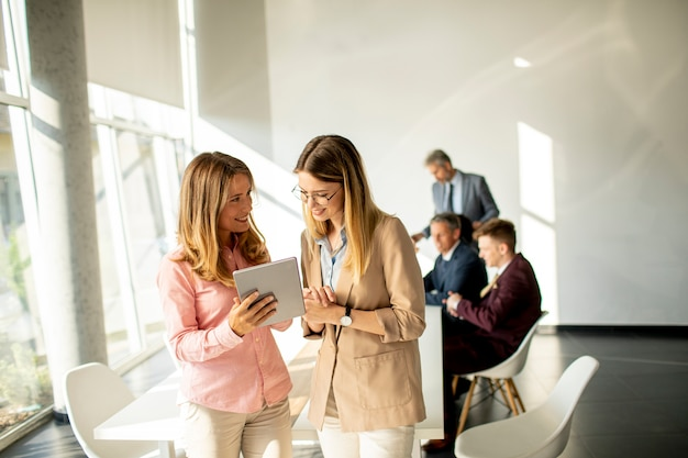 Две улыбающиеся молодые женщины, глядя на цифровой планшет в офисе