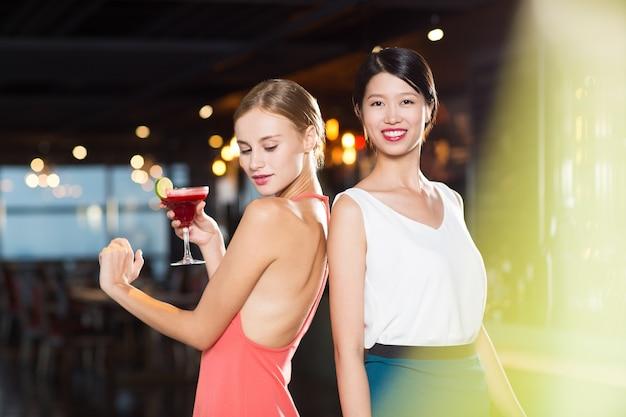Two smiling young women in nightclub