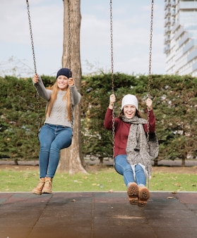 Две улыбающиеся молодые женщины на качелях