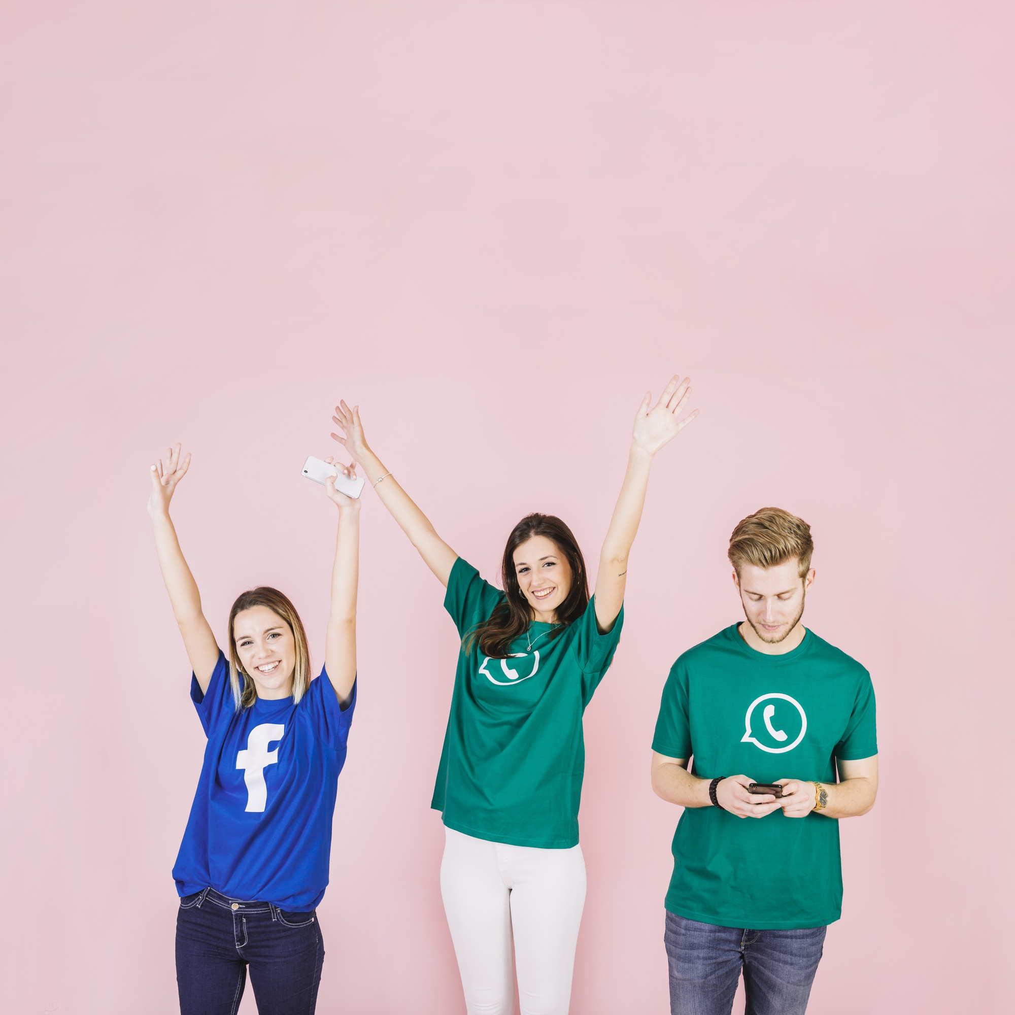 Two smiling young women raising their arms besides man using mobile phone