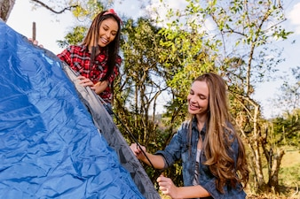 Two smiling young women setting blue tent