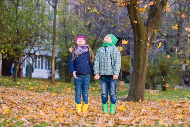 두 명의 smilling 아이들이 공원에서 단풍 나무 잎을 가지고 놀아요. 소년과 소녀는 낙엽을 응시합니다.