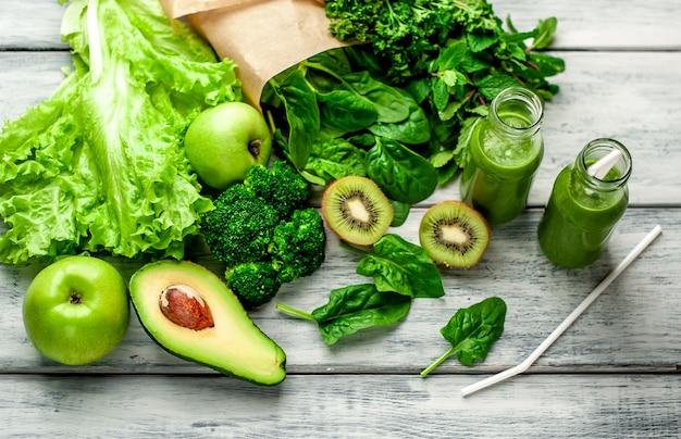 Два смузи с овощами, авокадо, яблоко, киви на деревянном фоне. спортивное питание