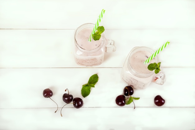 Two smoothies of cream and sweet cherry with mint in jars with straws