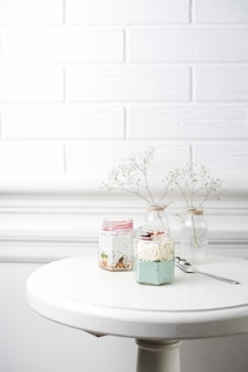 Two smoothies glass jars with spoon on table against white wall