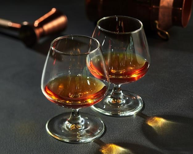 Два бокала с бренди на темно-серой каменной столешнице