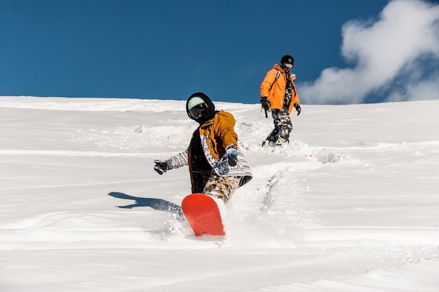 Two snowboarders in sportswear riding down the mountain slope