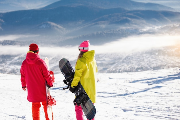 Two snowboarders stand and talk on the background of blue mountains.