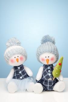 Two snowman dolls on gradient blue