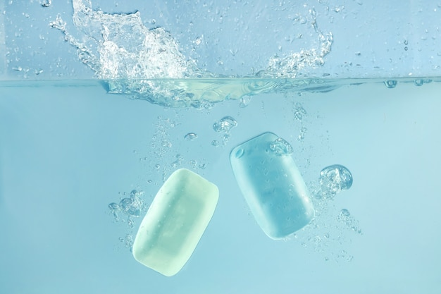 Two soap bars getting into water splash, clean concept
