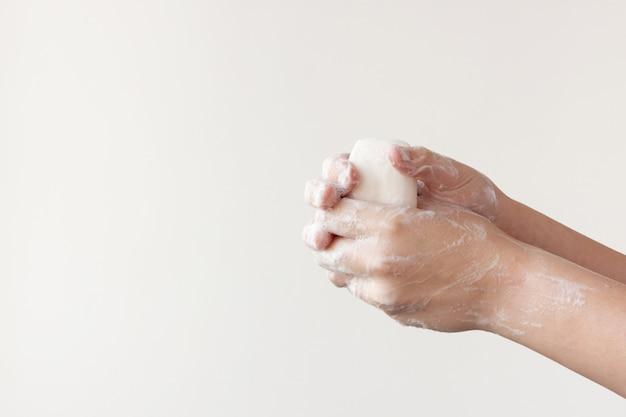 흰 바탕에 비누를 들고 있는 두 개의 비누 손이 주먹을 꽉 쥐고 있습니다. 질병을 예방하기 위해 손을 씻을 필요가 있다는 개념.