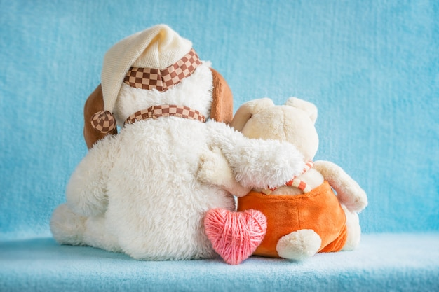 Two soft toy dog and rabbit embrace and pink heart on blue