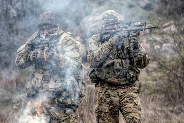 Два солдата в камуфляжной форме, с военной амуницией, прицеливаются из служебных винтовок, прикрывают друг друга, стреляют в конкурентов, атакуют врагов через дымовую завесу