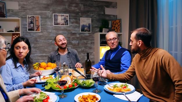 夕食時に父親と会話をしている2人の息子。おいしい食べ物。