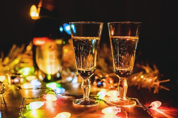 Два игристых бокала для шампанского, празднование нового года, рождественская праздничная концепция с украшениями для бутылок на деревянном столе, ветвях деревьев, свече. день святого валентина