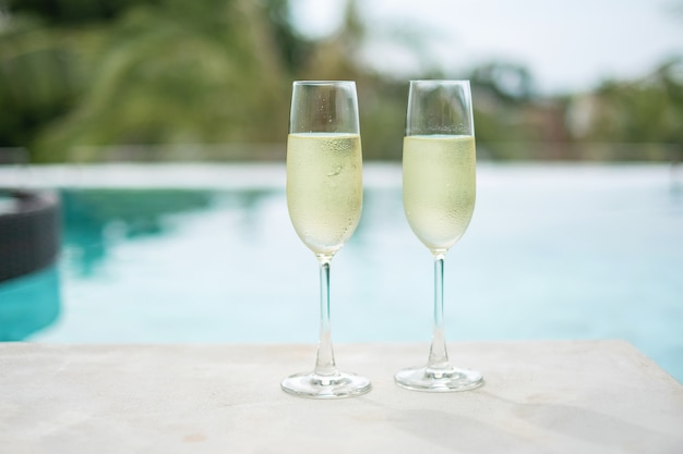 Two sparkling champagne glasses or prosecco near swimming pool
