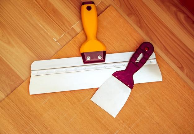 Два шпателя для домашнего ремонта. широкие и узкие инструменты на деревянных фоне.
