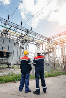 Two specialist electrical substation engineers inspect modern high-voltage equipment during sunset.