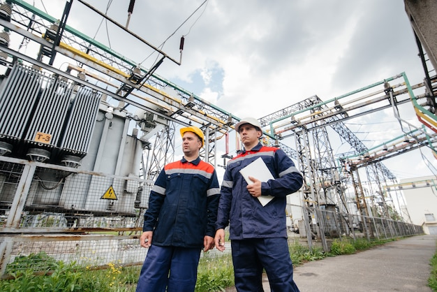 Two specialist electrical substation engineers inspect modern high-voltage equipment. energy. industry.