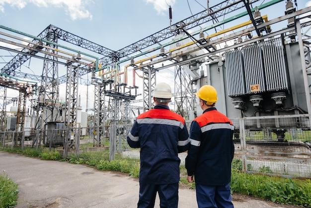 2人の専門の変電所エンジニアが最新の高電圧機器を検査します。エネルギー。業界。