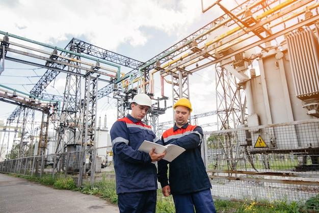 2人の専門の変電所エンジニアが夕方に最新の高電圧機器を検査します。エネルギー。業界。