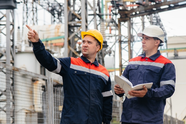 Two specialist electrical substation engineers inspect modern high-voltage equipment