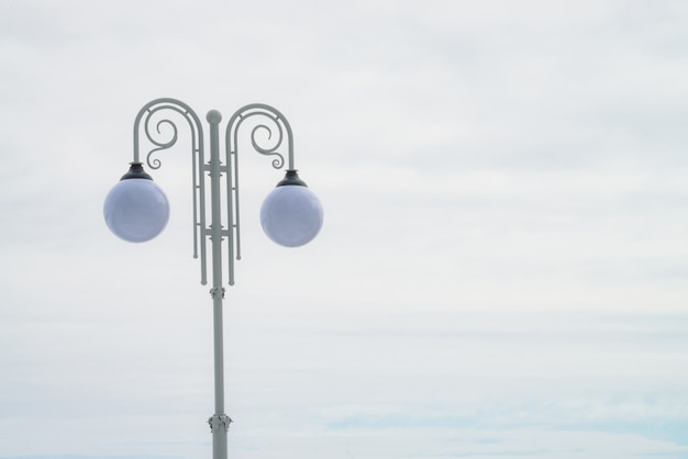 Two spherical street lamp on white vintage pillar on light sky background with copy space.