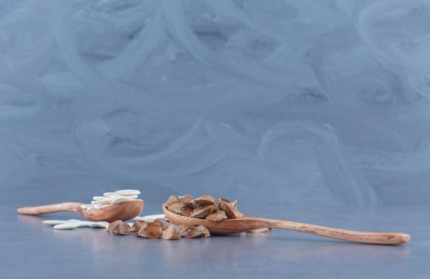 Due cucchiai di noccioli, su sfondo blu.