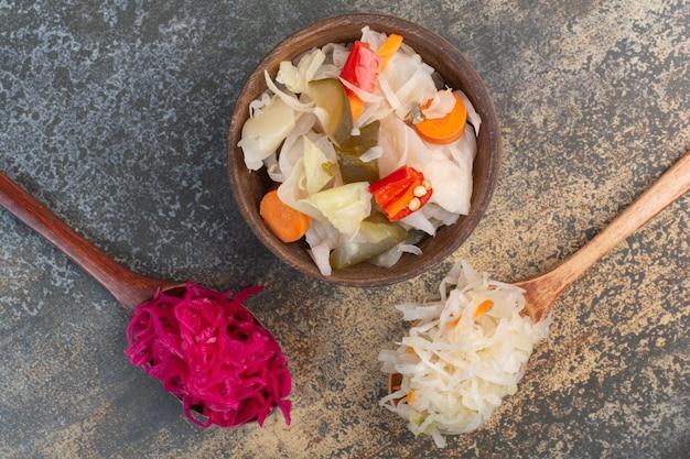 Две ложки капусты с деревянной миской соленых овощей. фото высокого качества