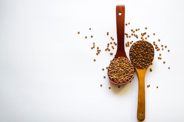 白い背景にレンズ豆のスプーン2杯健康的な食事は健康への鍵です