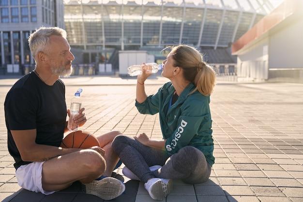 Два спортивных друга мужчина и женщина в спортивной одежде пьют воду во время отдыха после тренировки сидя