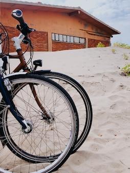 2台のスポーツバイクが白い砂浜に並んでいます。テンプレート空きスペースパターン壁紙モックアップ