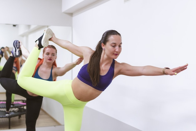 Две спортивные девушки занимаются прыжками на спортивном батуте.