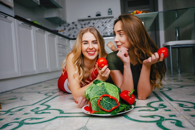 Two sports girls in a kitchen with vegetables