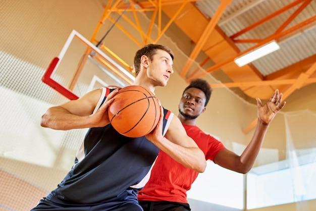 Two sportsmen playing basketball