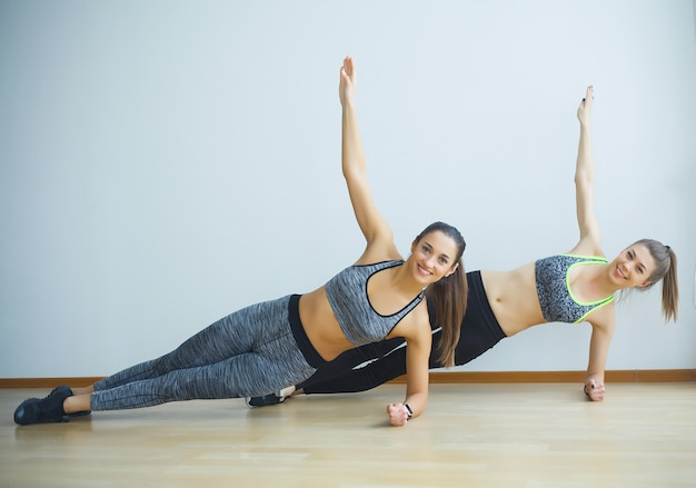 Two sporty girls doing exercises ups in gym
