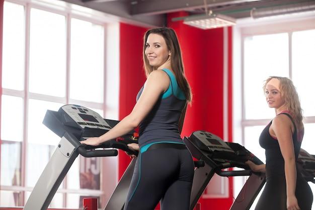 Two sporty girls walk on treadmill Free Photo