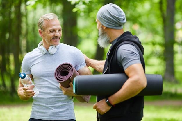 何かについて話しているマットを保持している公園のどこかに立っている2人のスポーティな成熟した大人の男性